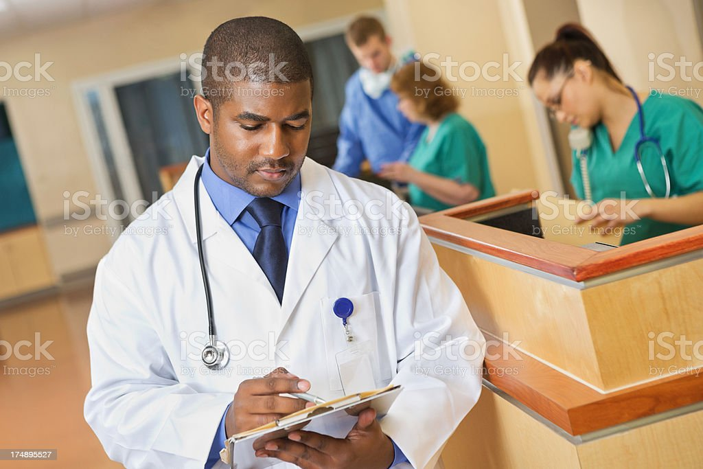 Doctor taking notes in hospital setting royalty-free stock photo