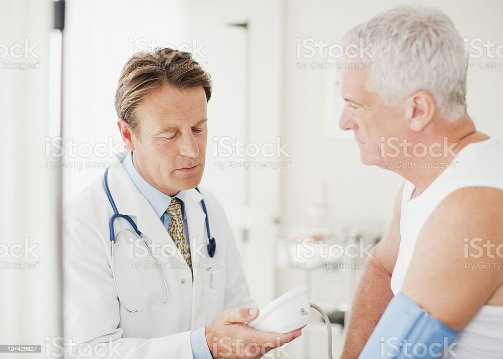 Doctor taking patients blood pressure in doctors office royalty-free stock photo