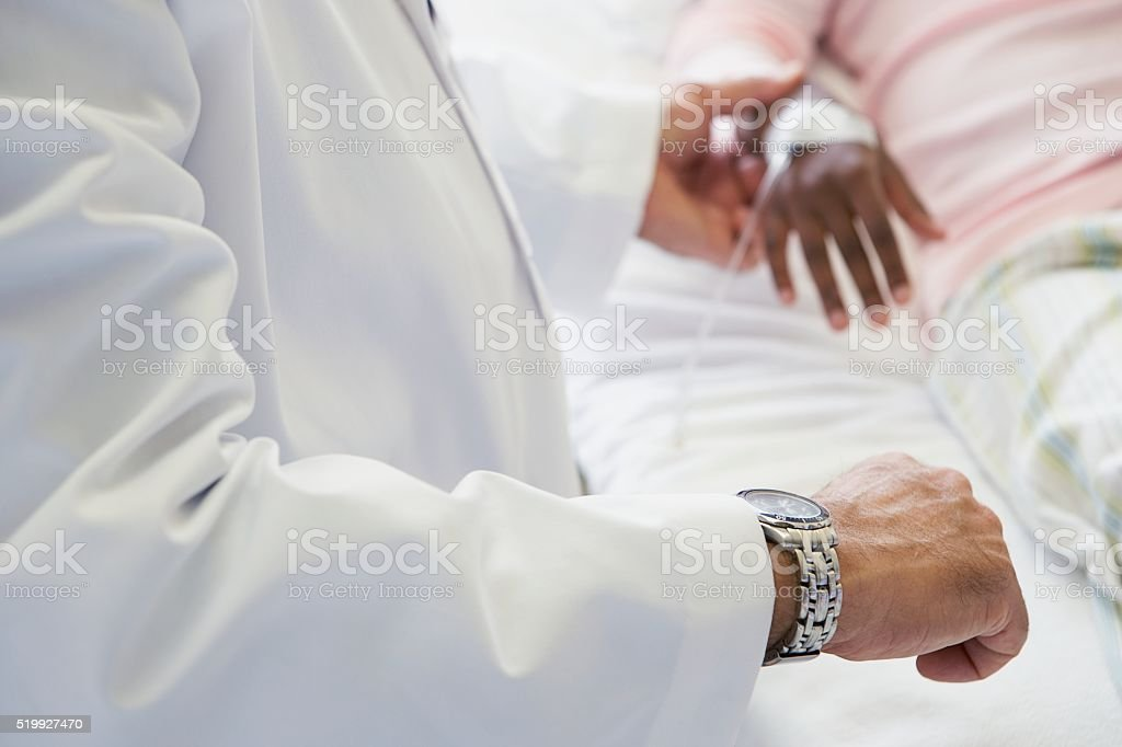 Doctor taking patient's pulse stock photo