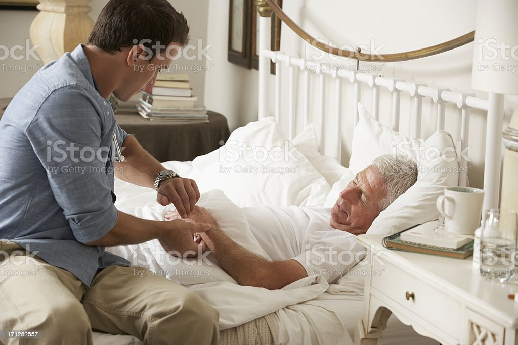 Doctor Taking Pulse Of Senior Male Patient In Bed stock photo