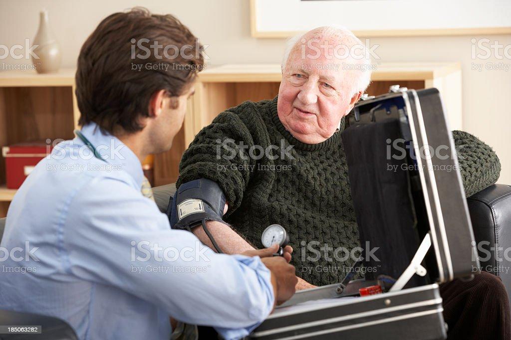 Doctor taking senior man's blood pressure at home stock photo