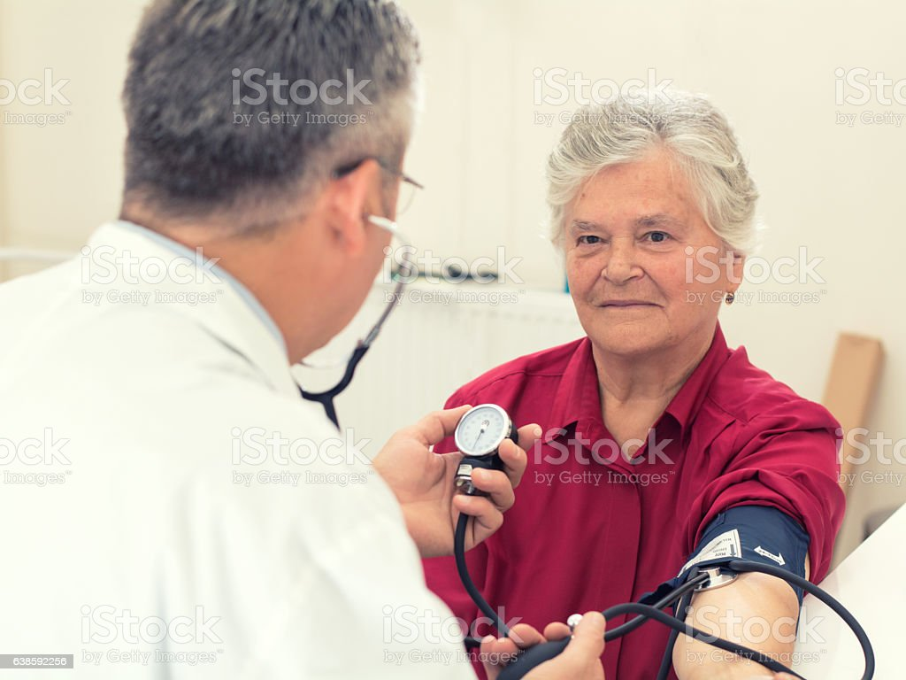 Doctor taking senior woman blood pressure stock photo