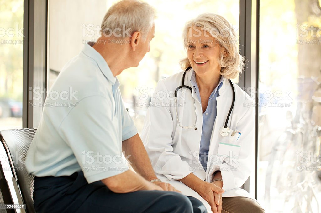 Doctor talking to a patient at the hospital stock photo