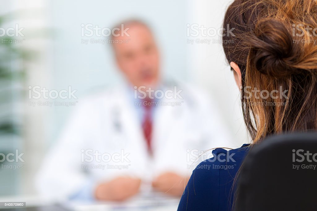 Doctor talking to a patient in his office stock photo