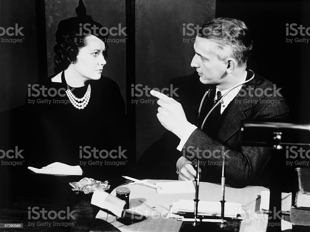 Doctor talking  to female patient, (B&W) royalty-free stock photo