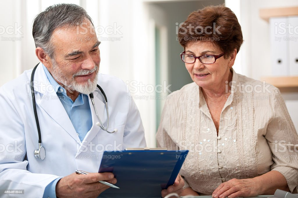 Doctor talking to his female senior patient stock photo