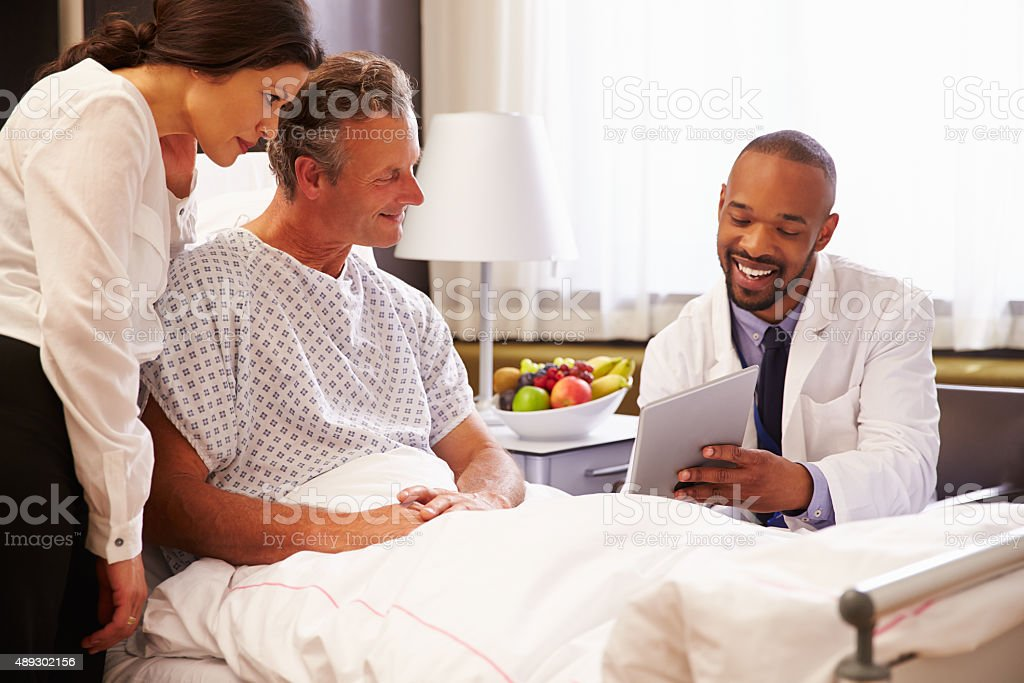 Doctor Talking To Male Patient And Wife In Hospital Bed stock photo