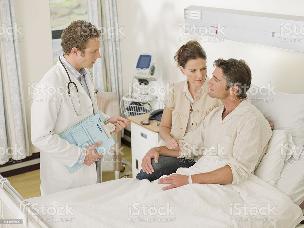 Doctor talking to patient and wife in hospital room royalty-free stock photo