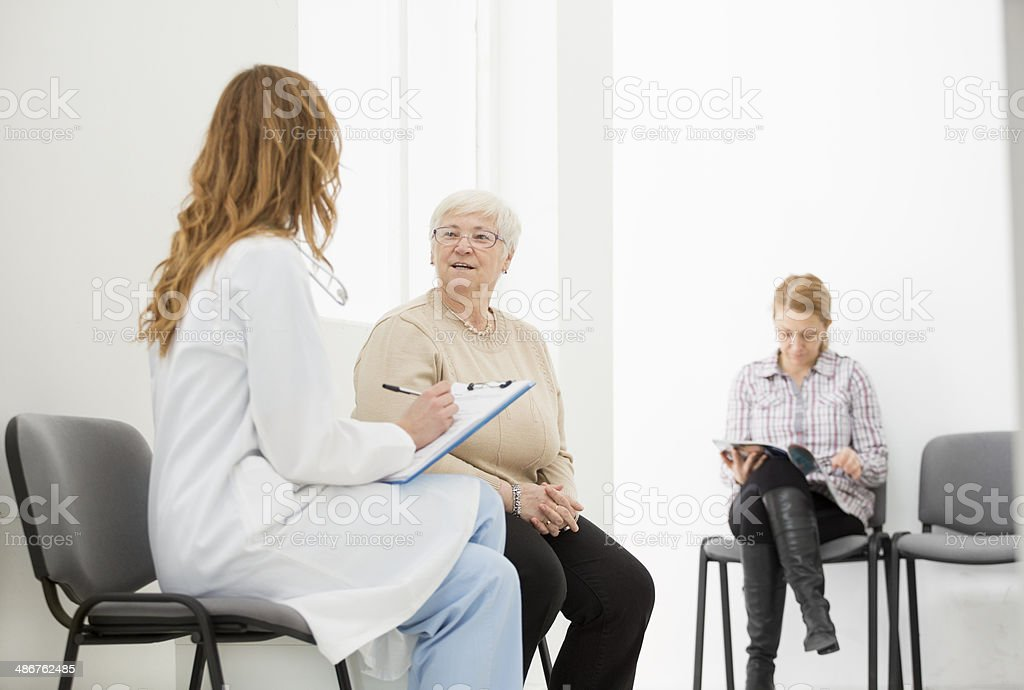 Doctor talking to patient in waiting room. royalty-free stock photo