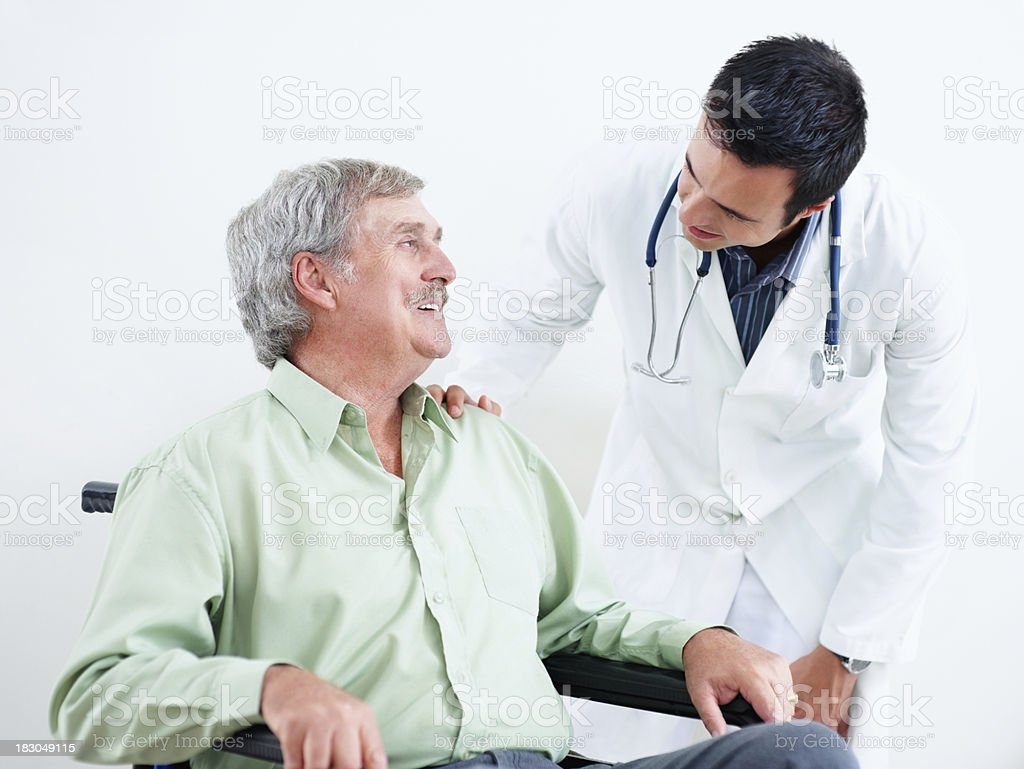 Doctor talking to senior patient in wheel chair against white royalty-free stock photo