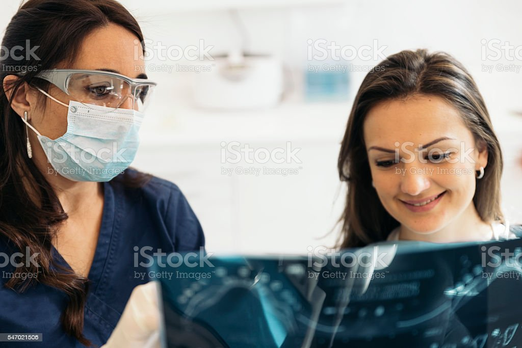 Doctor talking with her patient and teaching a radiograph. stock photo