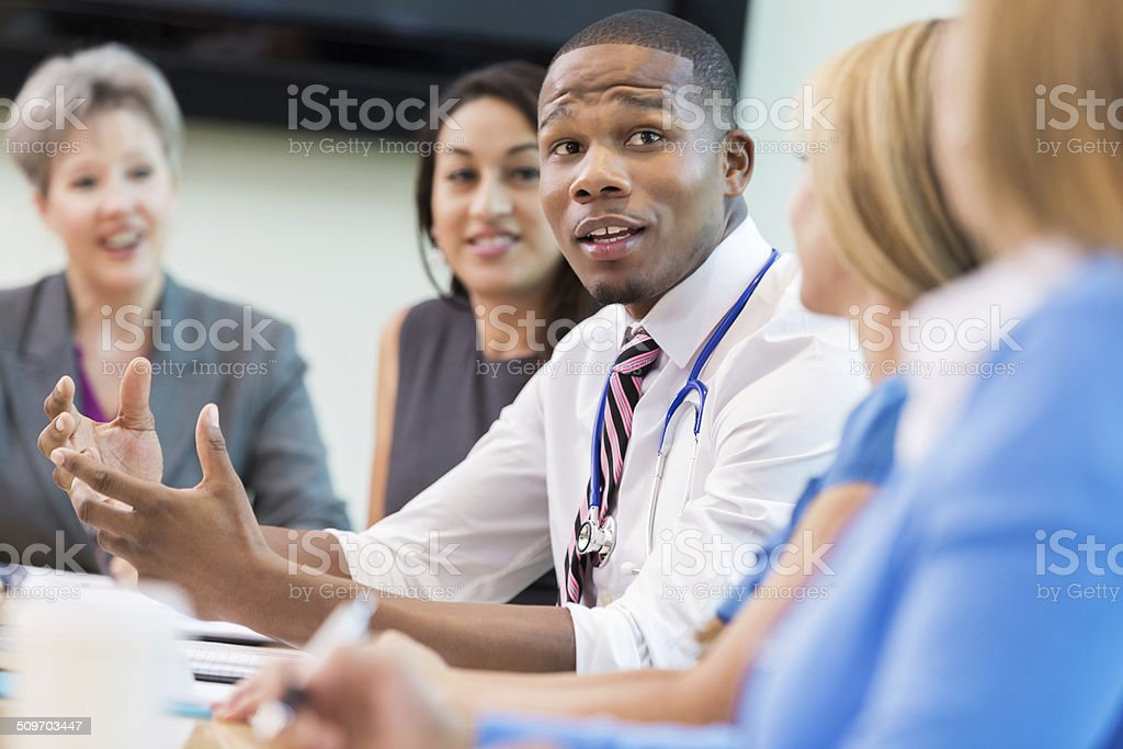 Doctor talking with hospital board members during meeting stock photo