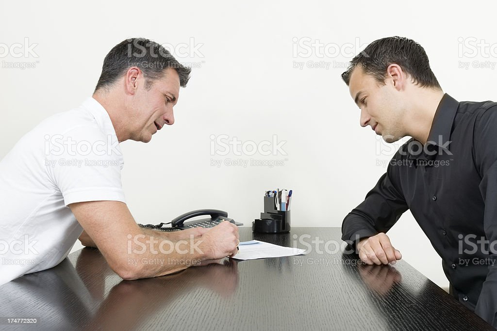 doctor talking with patient at desk stock photo