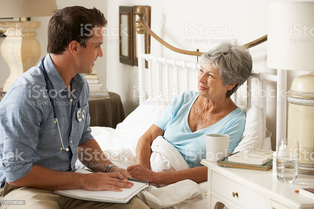 Doctor Talking With Senior Female Patient In Bed stock photo