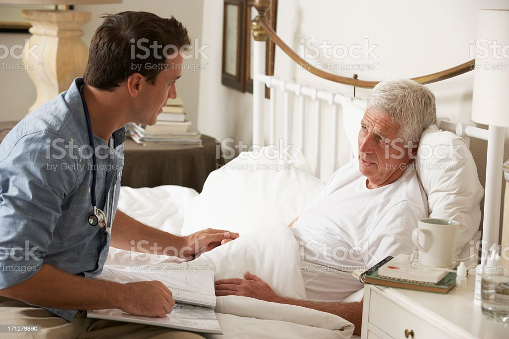 Doctor Talking With Senior Male Patient In Bed stock photo