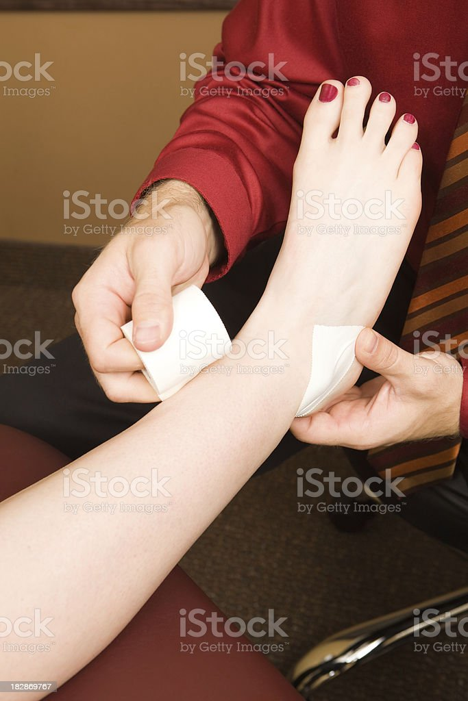 Doctor Taping a Woman's Ankle royalty-free stock photo