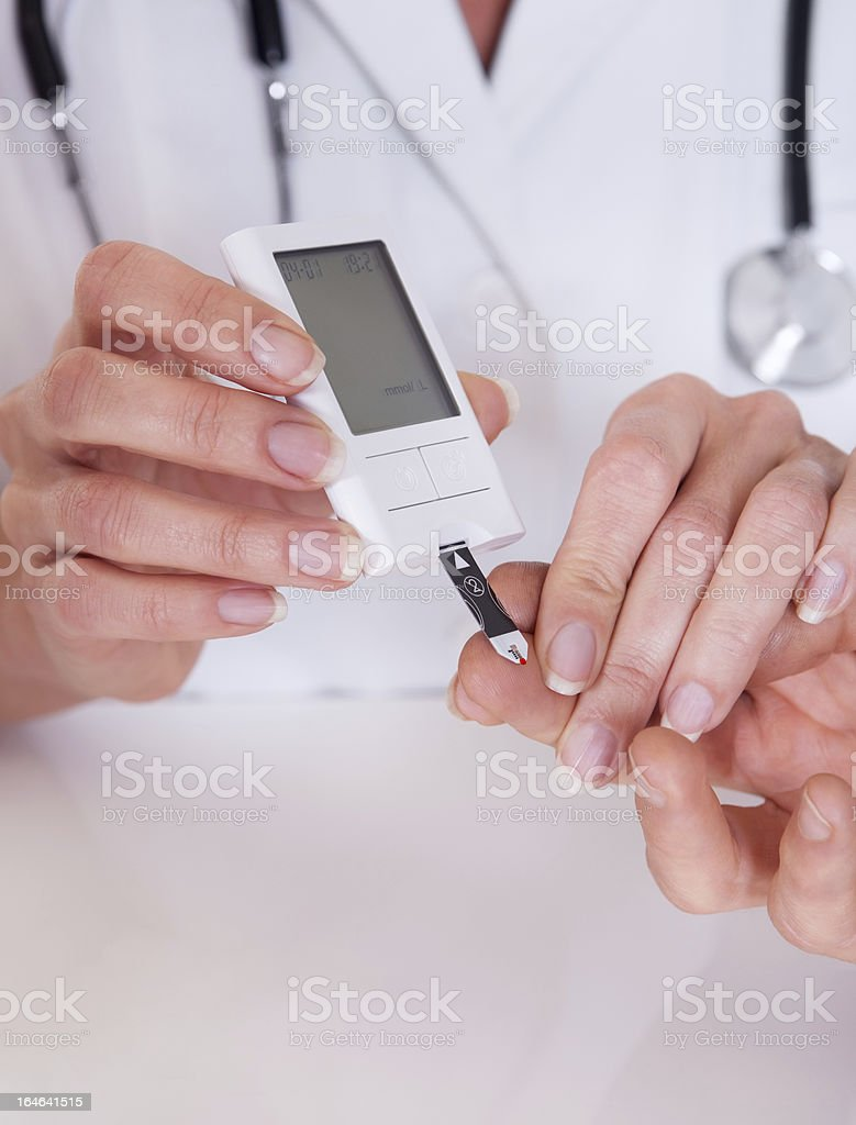 Doctor testing a patients glucose level royalty-free stock photo