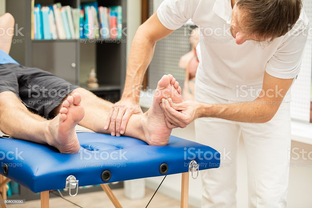 Doctor testing sensibility of foot stock photo