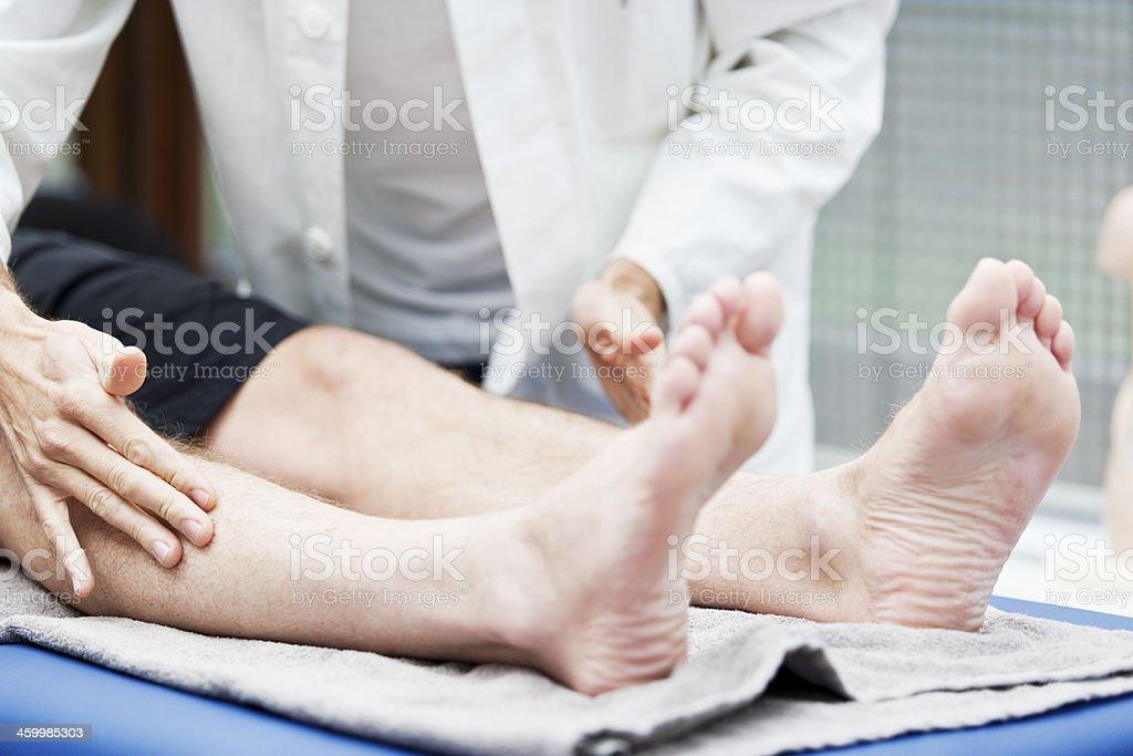 Doctor testing sensibility of leg stock photo