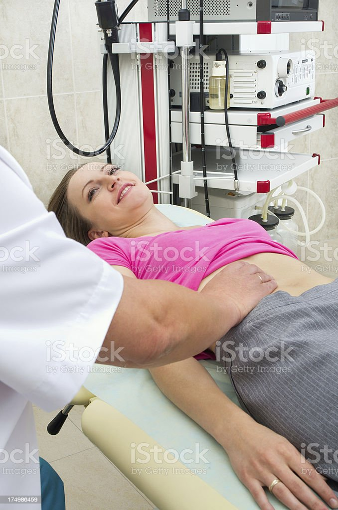 Doctor testing stomach of young woman royalty-free stock photo