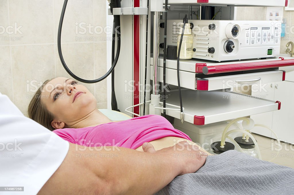 Doctor testing stomach of young woman stock photo