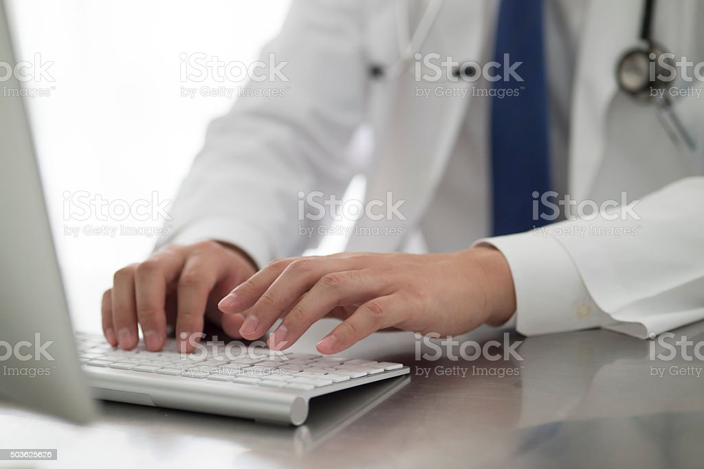 Doctor to operate the personal computer in the office stock photo