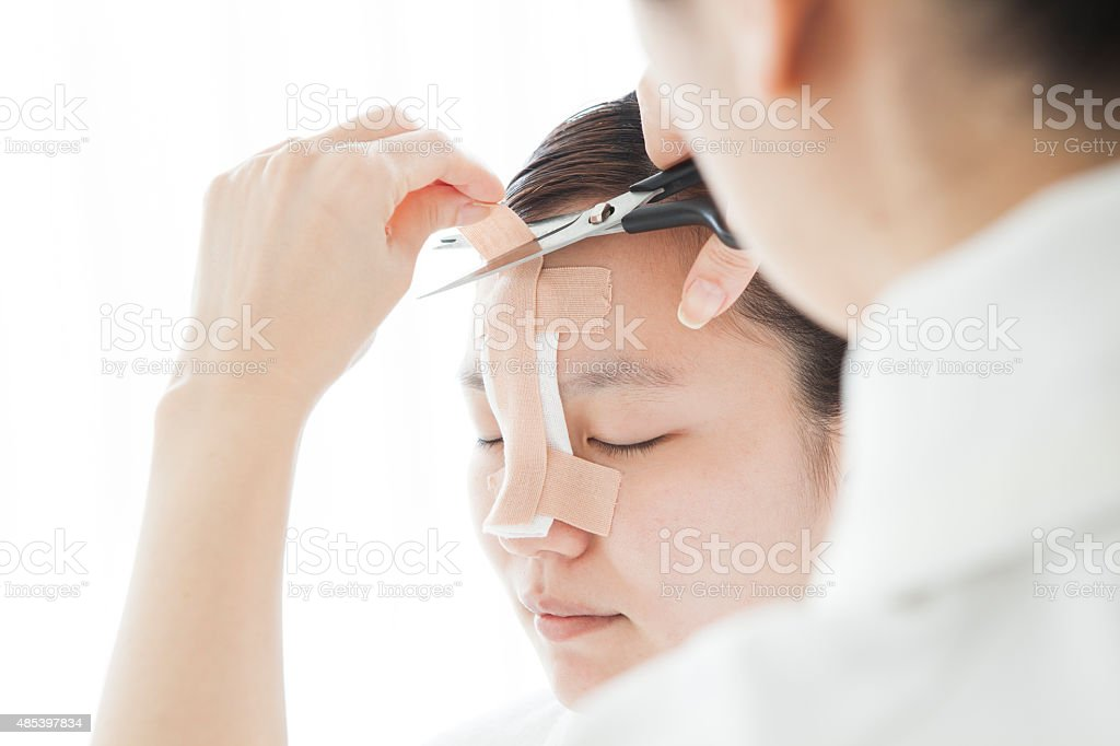 Doctor to taping a patient's nose stock photo