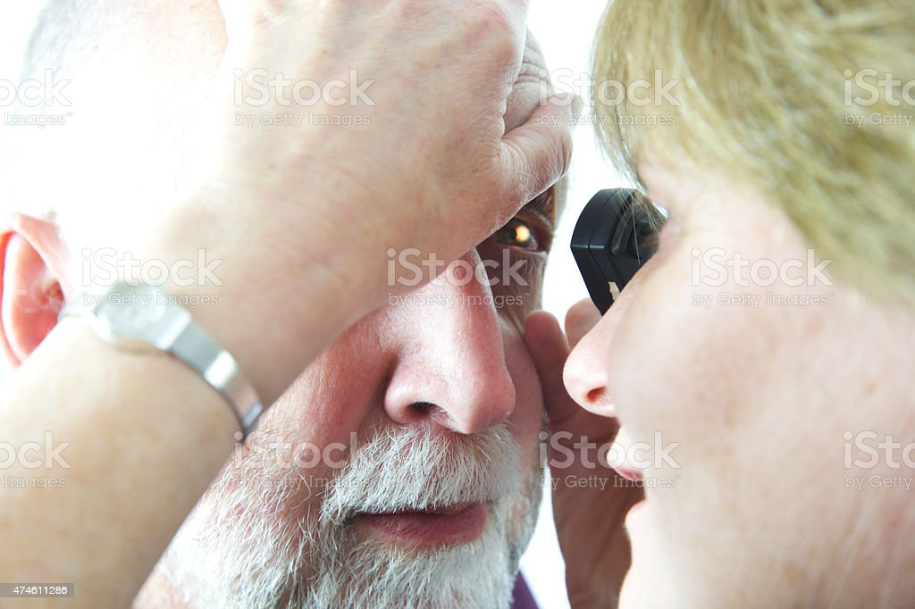 Doctor undertaking an eye examination with an opthalmoscope stock photo