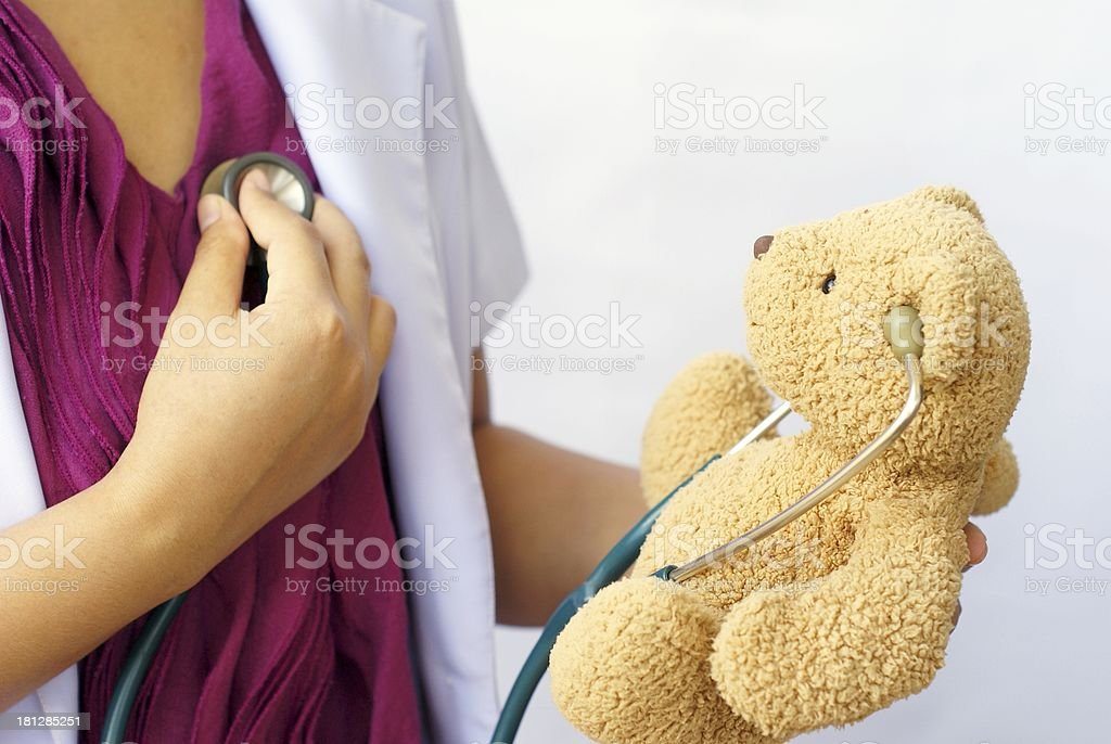 doctor, using a stethoscope with doll royalty-free stock photo