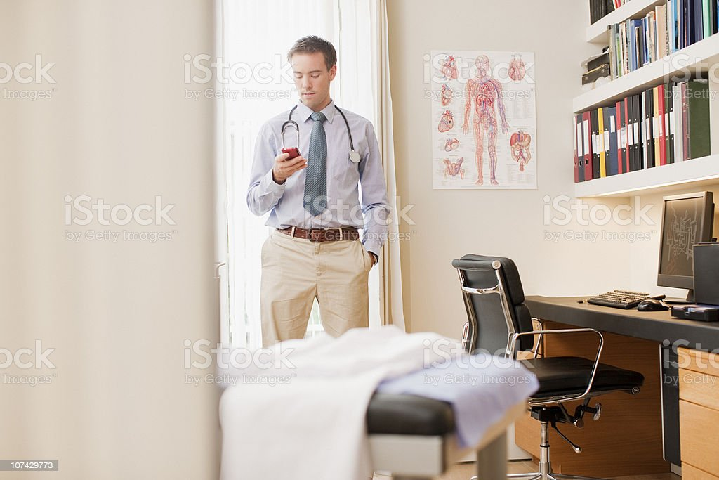 Doctor using cell phone in doctors office royalty-free stock photo