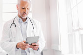 Doctor using digital tablet in brightly lit clinic