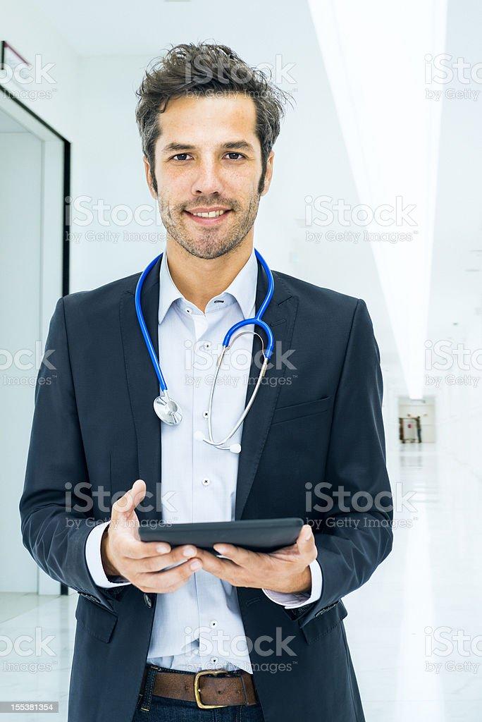 Doctor using digital tablet in hospital corridor stock photo