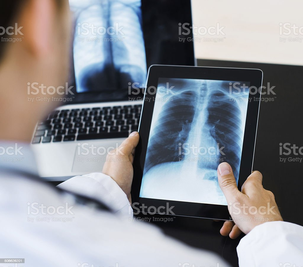 Doctor Using Digital Tablet Viewing Medical Scan stock photo