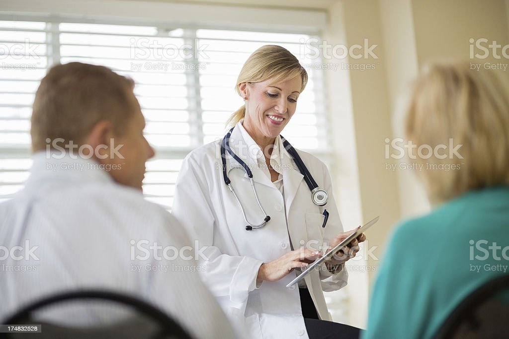 Doctor Using Digital Tablet With Couple In Foreground royalty-free stock photo
