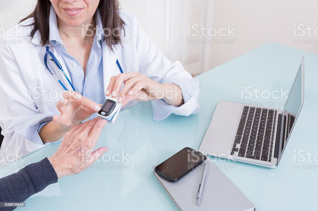 Doctor using finger oximeter with patient stock photo
