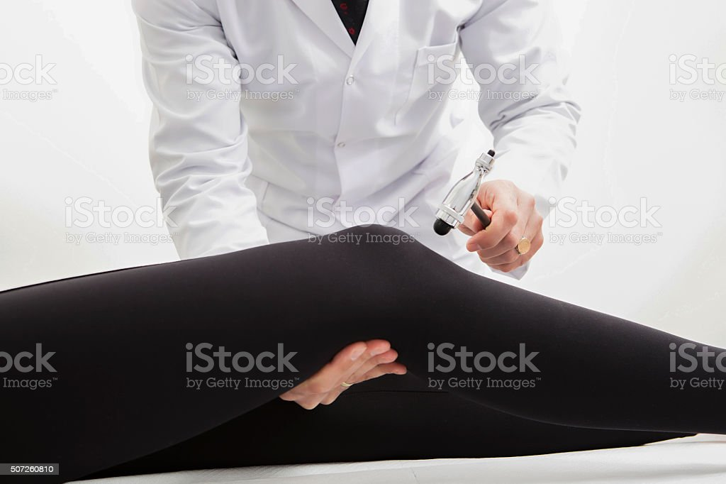 Doctor Using Knee Hammer on His Patient stock photo