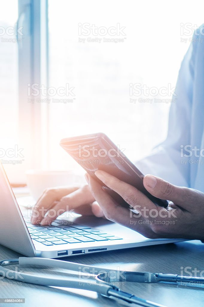 Doctor using smartphone and laptop in office stock photo