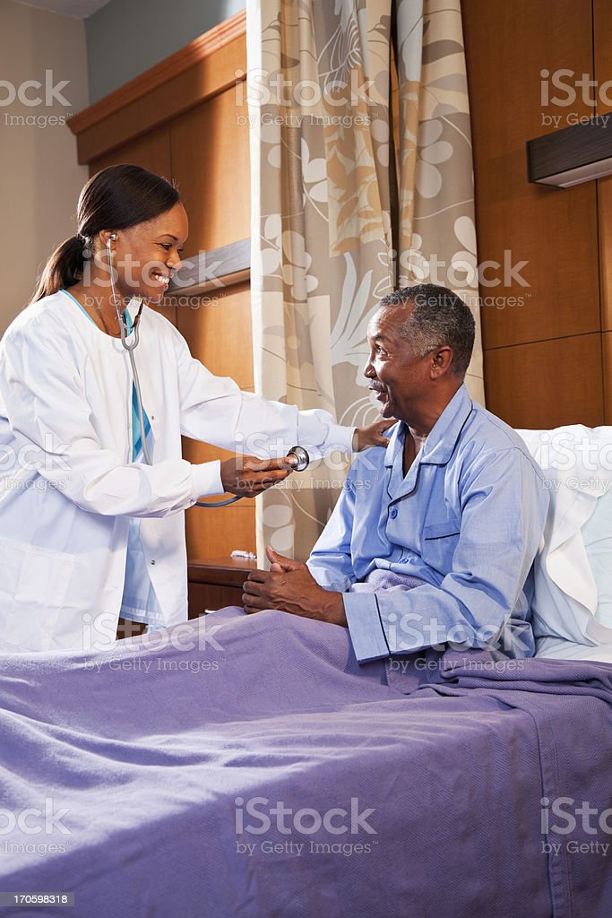 Doctor using stethoscope on senior patient royalty-free stock photo