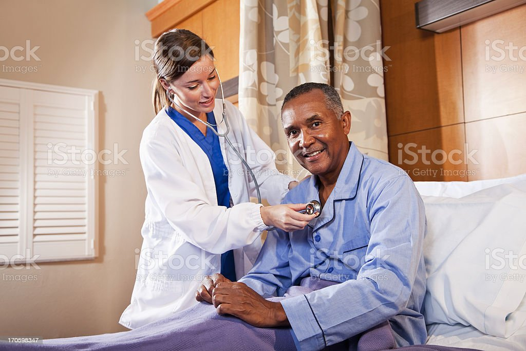 Doctor using stethoscope on senior patient stock photo