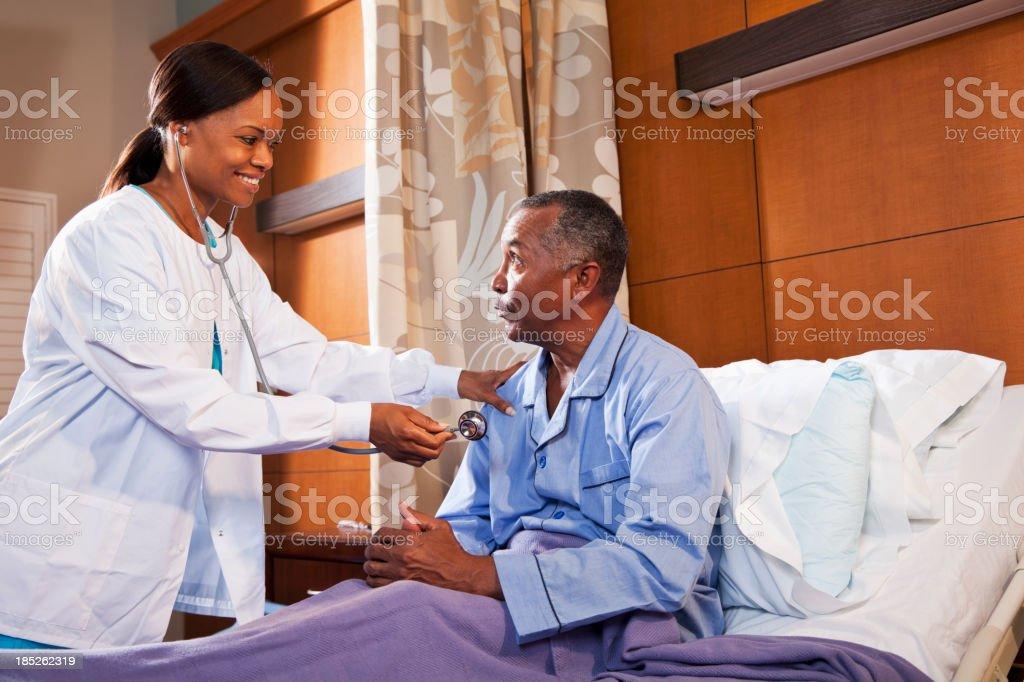 Doctor using stethoscope on senior patient stock photo