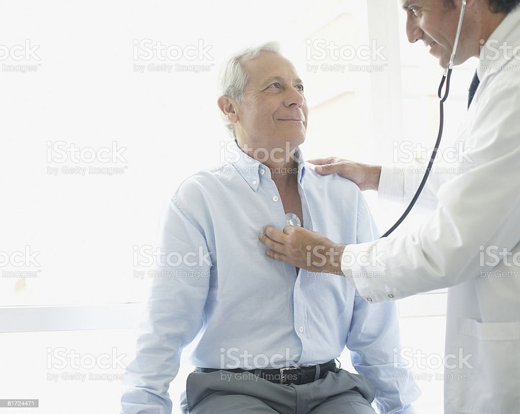Doctor using stethoscope on smiling patient stock photo