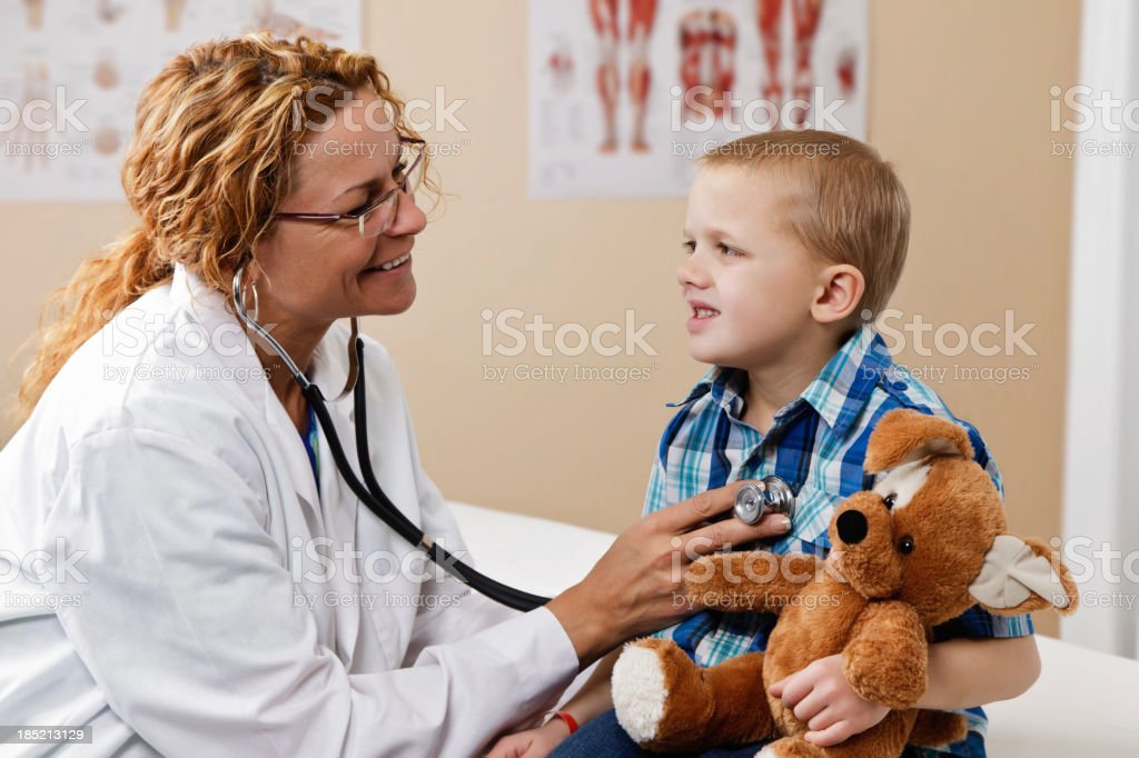 Doctor Using Stethoscope With Young Male Patient royalty-free stock photo