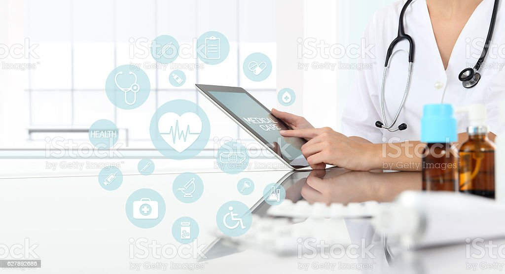 doctor using tablet in medical office with icons stock photo