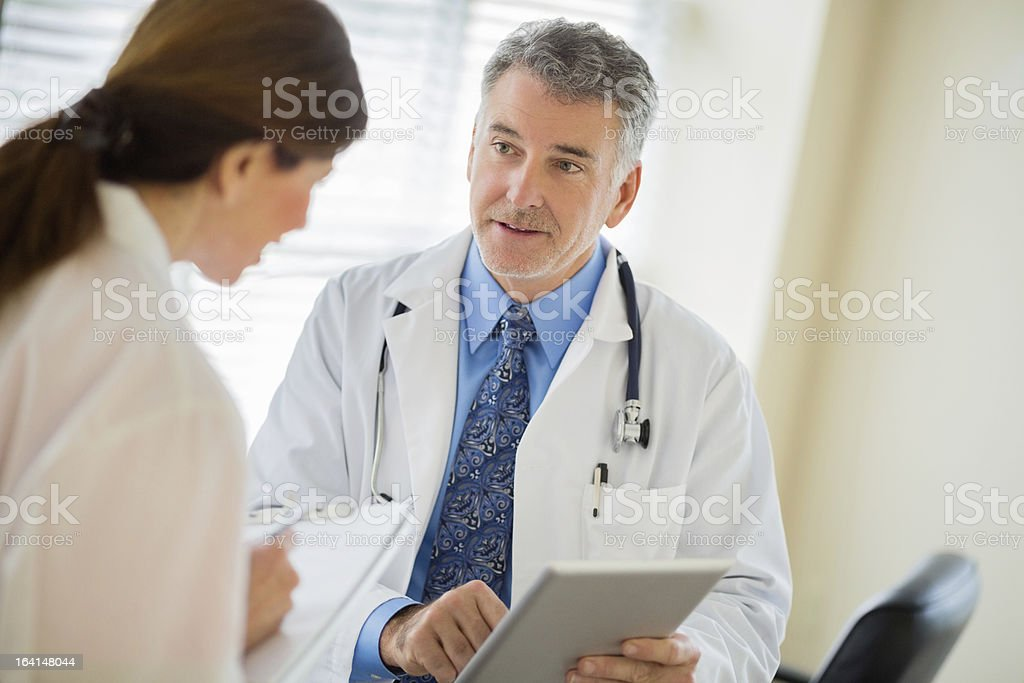 Doctor Using Tablet With Colleague Writing Notes royalty-free stock photo