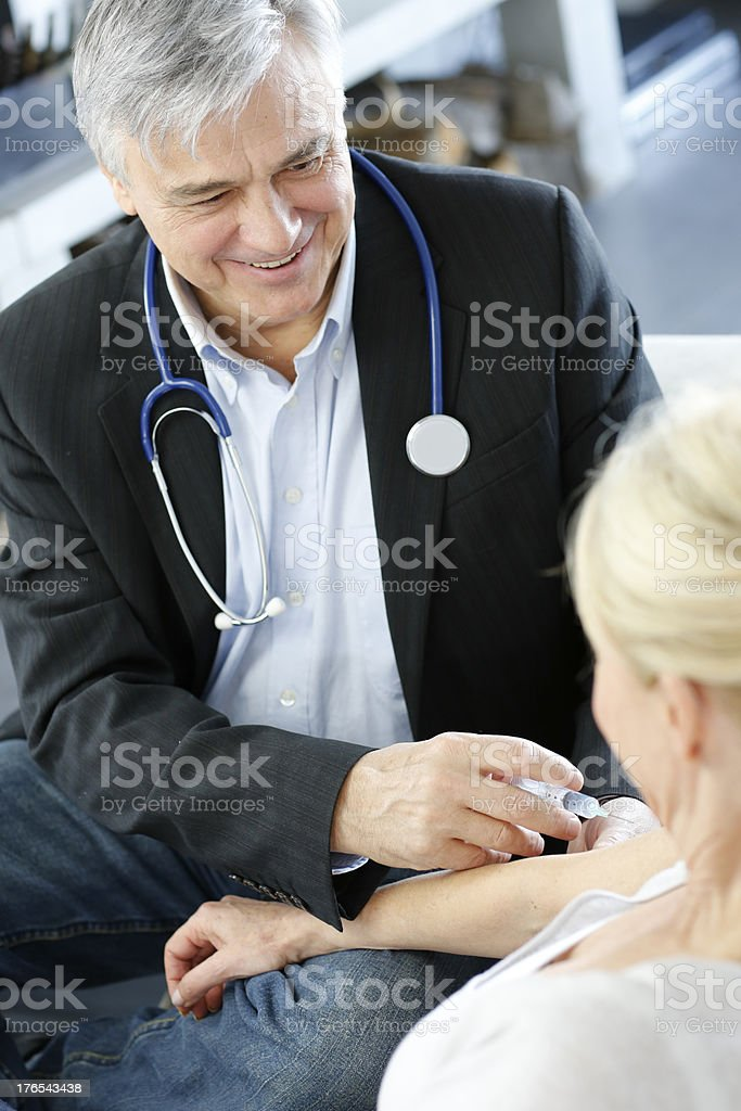Doctor vaccinating his patient at home royalty-free stock photo
