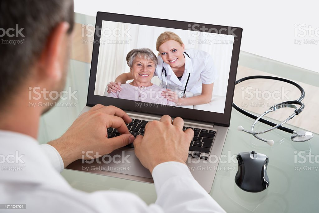 Doctor Video Chatting With Nurse And Patient stock photo