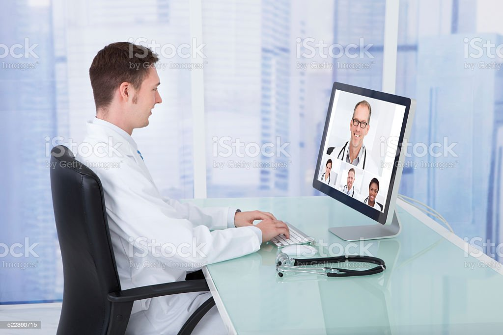 Doctor Video Conferencing With Colleagues Through Computer stock photo