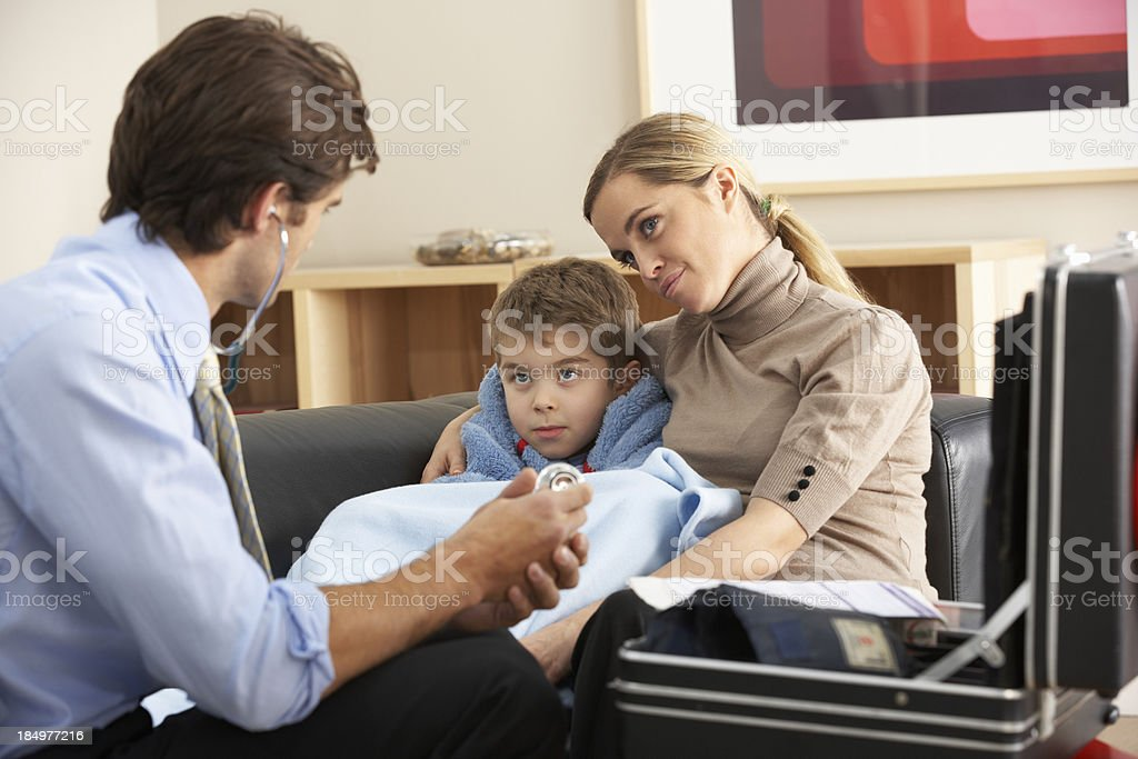 Doctor visiting sick child and mother at home stock photo