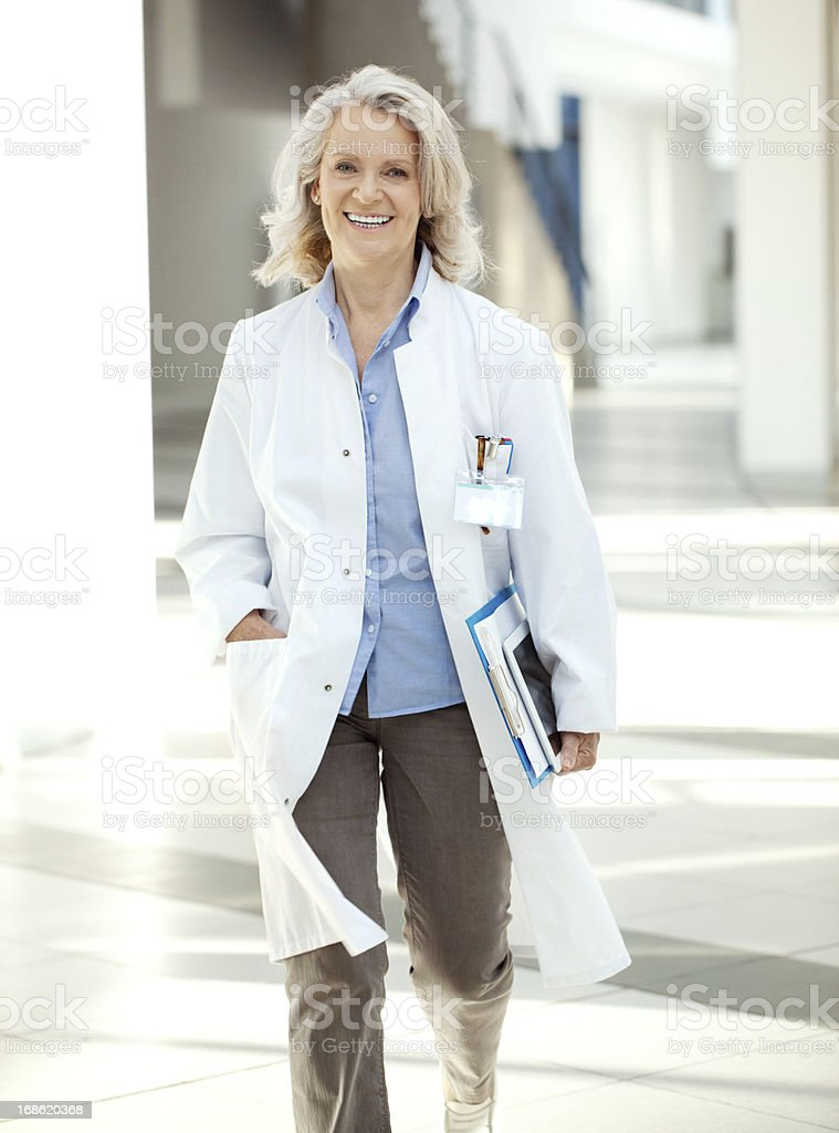 Doctor walking through the corrider of hospital with digital tablet stock photo