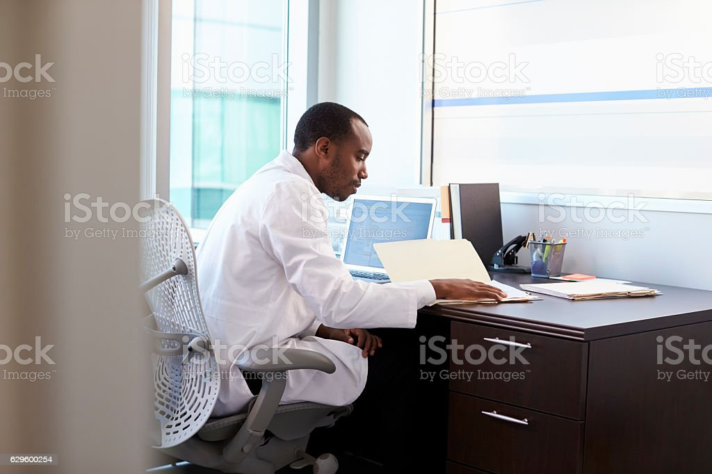 Doctor Wearing White Coat Reading Notes In Office stock photo ...